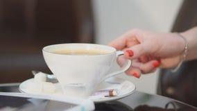 特写镜头 一件白色衬衣的女孩拿着一个杯子热的咖啡在与打好的奶油的上面在一块美丽的玻璃并且是 股票视频