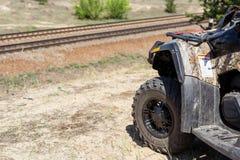 特写镜头ATV或方形字体站立在小山的自行车轮子 与铁路的美好的横越全国的风景在背景 极其 库存图片