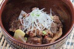 特写镜头Nikujaga包括牛肉,土豆和萝卜炖顶部用切的萝卜和薤在棕色陶瓷碗在makisu 免版税图库摄影