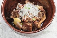 特写镜头Nikujaga包括牛肉,土豆和萝卜炖顶部用切的萝卜和薤在棕色陶瓷碗在washi 库存照片