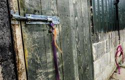 特写镜头o一个锁着的木门和大厦被看见在一个号衣围场 免版税库存照片