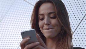 特写镜头potrait愉快和在输入电话和微笑的爱女孩 股票视频
