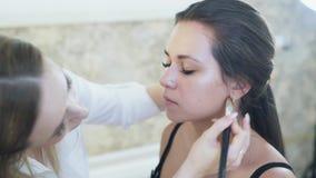 特写镜头stadikam构成专家在工作 化妆师申请口气于客户` s面孔,混和 股票视频