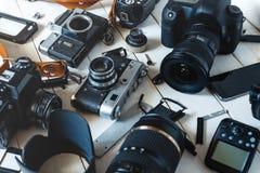 特写镜头、数字照相机、葡萄酒影片照相机、辅助部件和辅助部件白色木表面上 免版税库存照片