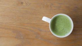 特写镜头一个杯子在干净的木桌上的热的绿茶在morni 图库摄影