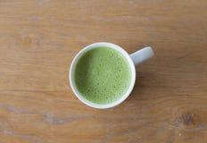 特写镜头一个杯子在干净的木桌上的热的绿茶在morni 免版税库存图片