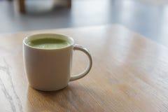 特写镜头一个杯子在干净的木桌上的热的绿茶在morni 库存图片