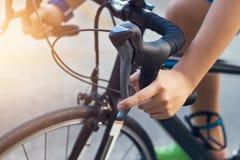 特写镜头一个年轻骑自行车的人的手和把手在街道上的 免版税库存图片