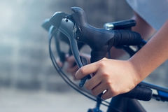 特写镜头一个年轻骑自行车的人的手和把手在街道上的 库存图片