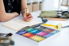 特写镜头一份女性画家图画草稿的角度图在写生簿的使用铅笔 速写在艺术演播室的艺术家与 免版税库存图片