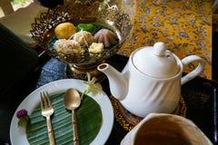 特写镜头下午茶时间套与香蕉叶子和花装饰的泰国传统点心在花卉样式桌布 免版税库存图片