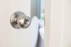 特写镜头不锈的门把手,与开放的门有一点 库存照片