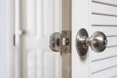 特写镜头不锈的门把手,与开放的门有一点 免版税库存照片