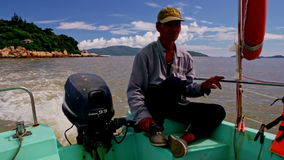 特写镜头人坐小船船尾控制引擎 影视素材