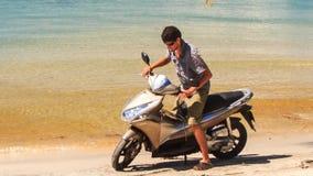 特写镜头人看看海上在金黄海滩的摩托车 股票录像