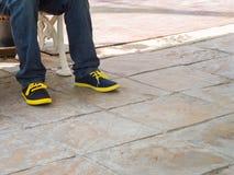 特写镜头人腿佩带蓝色牛仔裤裤子和运动鞋鞋子空间 图库摄影