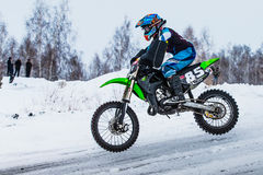 特写镜头人骑自行车的人在多雪的小山骑摩托车 库存图片