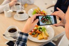 特写镜头人` s递拍食物的照片与流动巧妙的电话的 图库摄影
