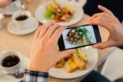 特写镜头人` s递拍食物的照片与流动巧妙的电话的 库存照片