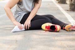 特写镜头伤害行程肌肉痛赛跑者连续体育运动弄脏大腿涉及 充满痛苦的妇女在脚腕,当跑步时 图库摄影