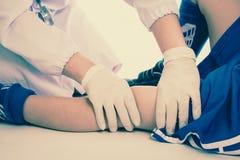 特写镜头伤害行程肌肉痛赛跑者连续体育运动弄脏大腿涉及 青年蓝色制服的足球运动员 关心健康联接膝盖按摩痛苦 免版税库存图片
