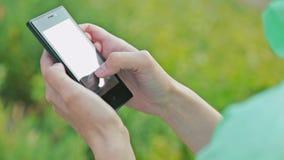 特写镜头使用户外触摸屏幕电话的妇女手 影视素材