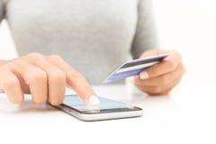 特写镜头使用电话和信用卡购物的妇女手 免版税库存照片