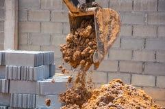 特写镜头到肮脏的挖掘机桶,倾吐的土壤 图库摄影