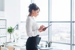 特写镜头发短信给,传送和读信息的雇员的侧视图画象在她的断裂期间在工作场所 免版税库存图片