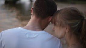 特写镜头后面视图 年轻恋人走沿湖的边缘的男人和妇女在日落 股票录像