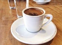 特写镜头咖啡和水在桌上 免版税库存图片