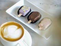 特写镜头咖啡杯和巧克力块在桌上 免版税库存照片