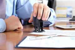 特写镜头商人手按在文件的一张邮票在办公室 免版税图库摄影