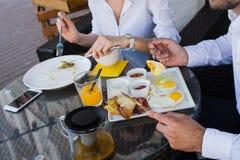 特写镜头商人手,男性和女性吃早餐在户外咖啡馆 饭食用沙拉,煎蛋卷,烟肉 库存照片