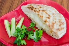 特写镜头土耳其多士(Tost),敬酒的三明治用切达干酪在有菜的红色板材服务在木桌上 库存照片