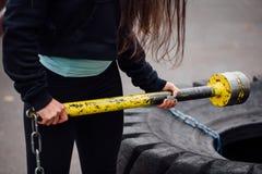 特写镜头在公园的女孩手有在拖拉机的锤子的疲倦背景 免版税库存照片