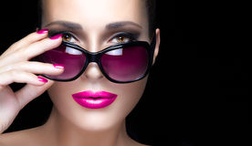 特写镜头在桃红色过大的太阳镜的妇女面孔 构成和玛尼 免版税库存照片