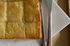 特写镜头在白色盘的topview面包在与刀子的木桌上 库存图片