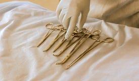 特写镜头在白色背景和解剖刀的隔绝的医生手四把不同不锈钢外科镊子 库存照片