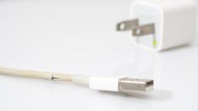 特写镜头在白色背景的残破的充电器缆绳 免版税库存图片