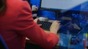 特写镜头在红色打扮的后侧方妇女研究计算机 股票录像