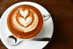 特写镜头在老棕色木ba的咖啡拿铁艺术和上等咖啡 图库摄影