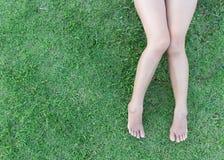 特写镜头在草背景的妇女腿 免版税库存图片