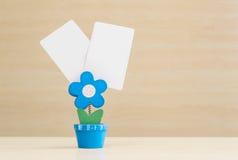 特写镜头在蓝色花形状形状的钳位照片在与黑白皮书的花盆在被弄脏的木书桌和墙壁背景 库存照片