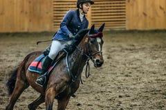 特写镜头在马背上女孩车手在复杂的体育的领域 免版税库存图片