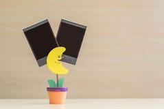 特写镜头在黄色月亮形状的钳位照片在与黑空白的影片的花盆在被弄脏的木书桌和墙壁背景 免版税库存照片