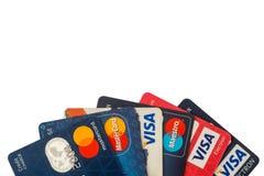 特写镜头堆信用卡、签证和万事达卡、信用,借方和电子 查出在与裁减路线的空白背景 免版税库存图片