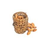 特写镜头堆干坚果,能量食物,与在与裁减路线的白色背景隔绝的木柳条制品的杏仁 免版税库存图片