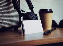 特写镜头堆白纸名片大模型木头表 拿走咖啡杯Coworking演播室 现代的耳机 库存照片