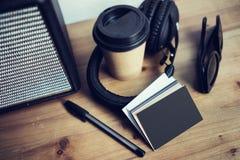特写镜头堆空白黑色纸名片大模型木头表 拿走咖啡杯Coworking演播室 现代的耳机 库存照片